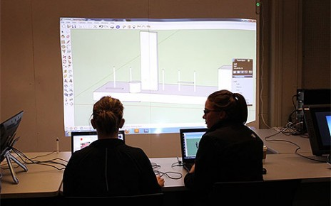 Two students in the Architectural Studies iLab, looking at a drawing on a projector