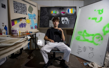 Zach Johnson sits in front of his artwork in his MU studio.