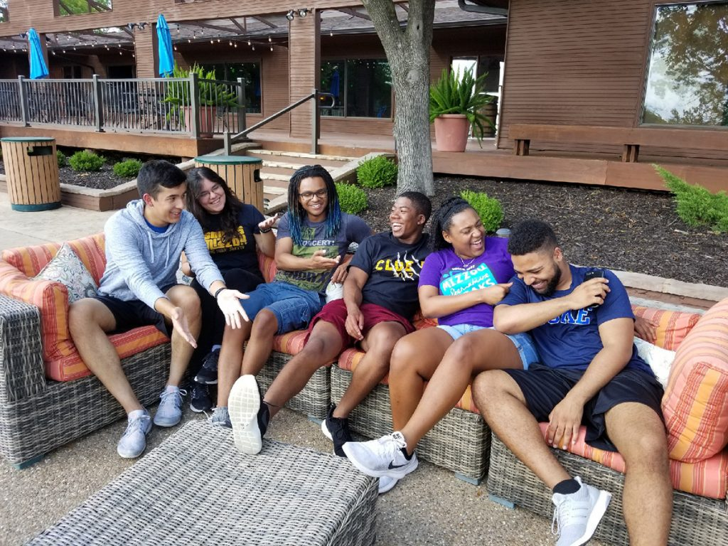 Students laugh while posing for a group photo on a couch