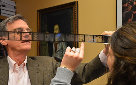 Berkley Hudson looking at newspapers on film strips with a student